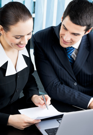 Two young happy smiling successful businesspeople signing document or contract at office. Business situations concept. Stock Photo