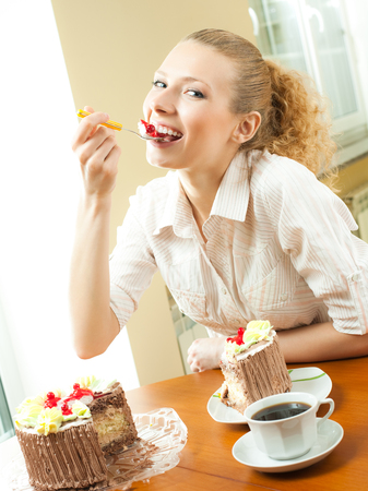 Young happy smiling beautiful woman eating torte at home. Healthy eating and dieting concept. Stock Photo
