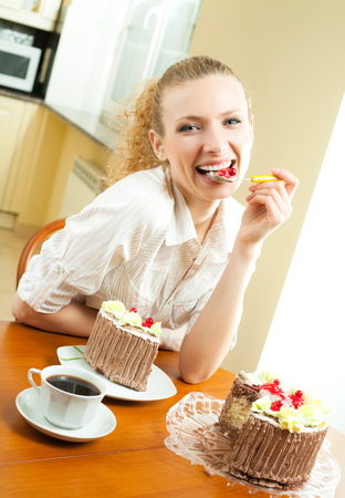 Young happy smiling beautiful young woman eating torte at home. Healthy eating and dieting concept.