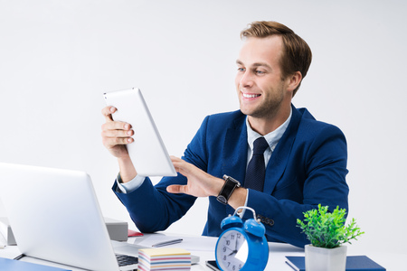 optimismo: Young happy smiling businessman in blue suit working with tablet computer at office. Success in business, job and education concept shot.