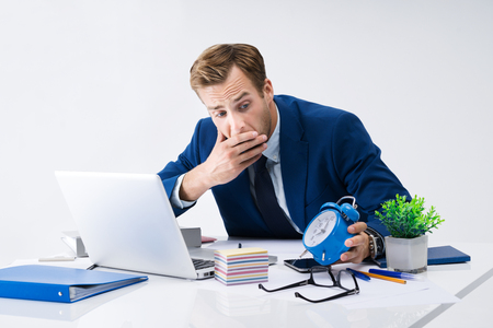 Busy businessman looking at alarm clock, in blue suit working with laptop computer at office. Success in business, job and education concept shot. Stock Photo