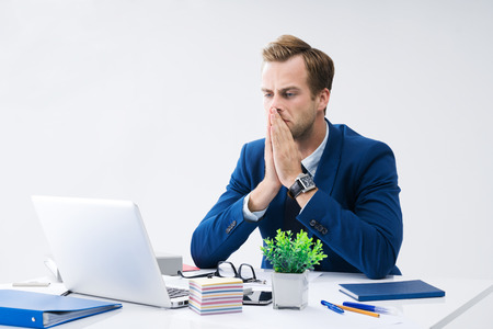 Stressed or hardly thinking businessman in blue suit, working with laptop computer at office. Business, job and education concept.