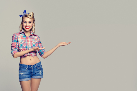Young happy smiling woman, dressed in pin-up style, showing something or copyspace area for text or slogan. Caucasian blond model posing in retro fashion and vintage concept studio shoot, on grey background. Stock Photo