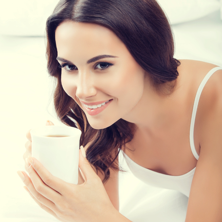 Portrait of young smiling woman drinking coffee or tea, at home