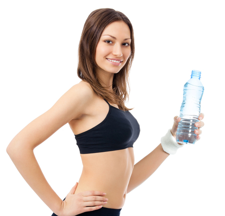 Portrait of happy smiling young woman in fitness wear with bottle of water, isolated over white background. Healthy lifestyle and individual sports concept. Stock Photo