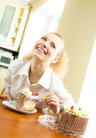 Young happy smiling beautiful young woman eating torte at home