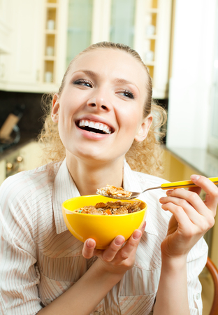 Young smiling woman eating muslin at home