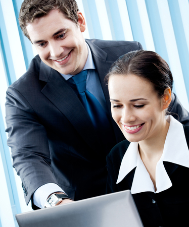 Two happy smiling cheerful young businesspeople working with laptop at office. Success in business concept.