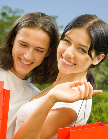 Young happy smiling attractive couple with red shopping bags outdoor. Love, romantic and relations concept.