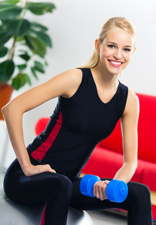 Portrait of young happy smiling woman in sportswear, doing fitness exercise with dumbbell on fit ball, at home. Healthy lifestyle, training and individual sports concept. photo