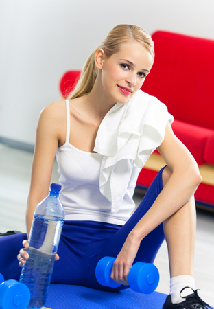 Woman in sportswear with dumbbells, bottle of water and terry towel, at home. Healthy lifestyle, training and individual sports concept. photo