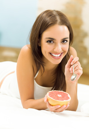 Portarit of young happy smiling beautiful woman eating grapefruit on bed, at home Stock Photo