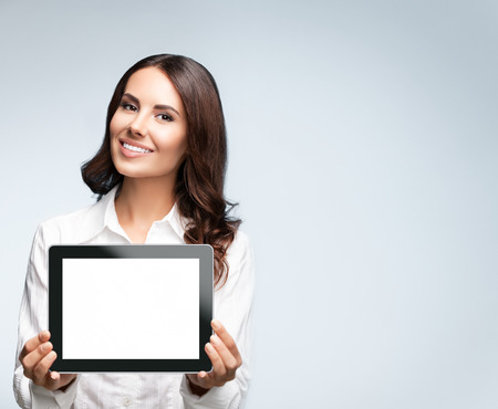 Portrait of cheerful beautiful young brunette businesswoman showing blank no-name tablet pc monitor, over grey background, with copyspace area for slogan or text message. Success in business concept studio shot.