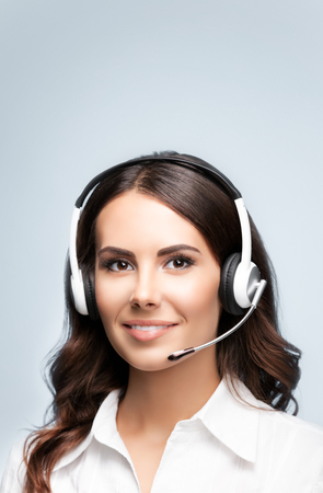 operator: Female customer support phone operator in headset, with blank copyspace area for slogan or text message, over grey background