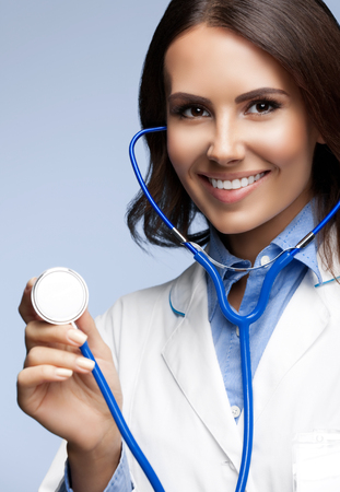healthcare portrait: Portrait of happy smiling female doctor with stethoscope in hand, on grey background. Healthcare, medical exam and lab concept.