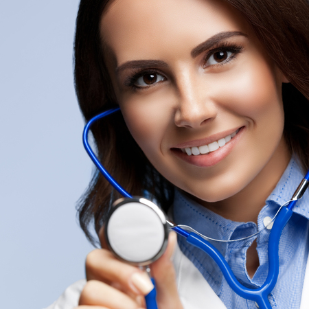 Portrait of happy smiling female doctor with stethoscope in hand, on grey background. Healthcare, medical exam and lab concept.