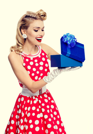 Portrait of beautiful young happy woman dressed in pin-up style red dress in polka dot and white gloves. Caucasian blond model posing in retro fashion studio shoot.