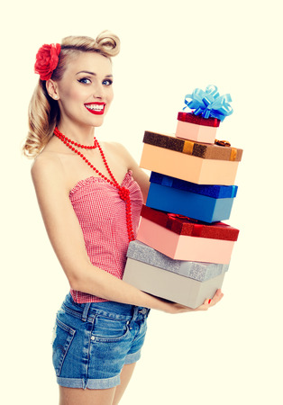 Portrait of beautiful young happy smiling woman in pin-up style clothing, holding gift boxes. Caucasian blond model posing in retro fashion and vintage concept shoot.