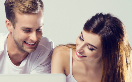 Beautiful young amorous couple using laptop, on bed. Caucasian models - internet, technology, family, love, relationship, happiness, concept shot.