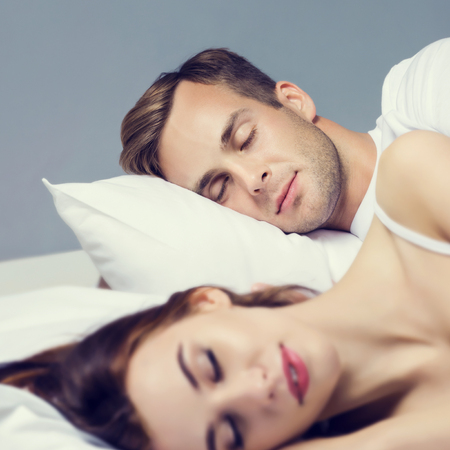 Young couple sleeping on the bed in bedroom. Caucasian models - in love, relationship, dating, happy people, bedtime concept shot.