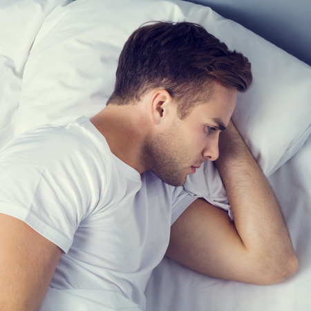 Unhappy young man on the bed in bedroom. Caucasian model - in insomnia, sad, crisis, frustrated concept shot. Stock Photo