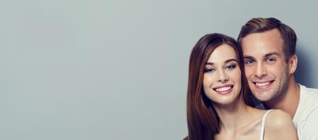 Retrato de la joven pareja, que le mira. modelos de raza blanca - amor, relación, el fechar, amantes felices, concepto, en contra de gris, con copia espacio para el lema o mensaje de texto. la composición de banner horizontal.