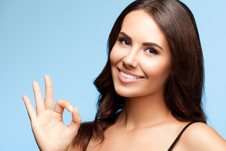 only 1 woman: portrait of beautiful young smiling brunette woman showing okay gesture, on bright blue background Stock Photo