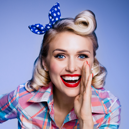 Portrait of beautiful young happy smiling woman, dressed in pin-up style. Caucasian blond model posing in retro fashion and vintage concept studio shoot, on blue background. Stock Photo