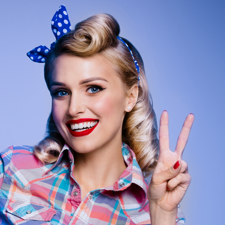 Portrait of beautiful young happy smiling woman, showing two fingers or victory gesture, dressed in pin-up style. Caucasian blond model posing in retro fashion and vintage concept studio shoot, on blue background. Stock Photo