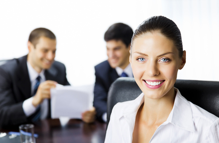 Portrait of happy smiling young businesswoman and colleagues on background, at office. Success in business and teamwork concept. photo