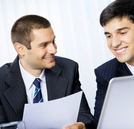 Two young happy smiling successful businesspeople working with document or contract at office. Success in business and teamwork concept. photo