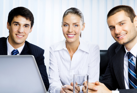 Portait of three happy smiling successful businesspeople at office. Success in business and teamwork concept.