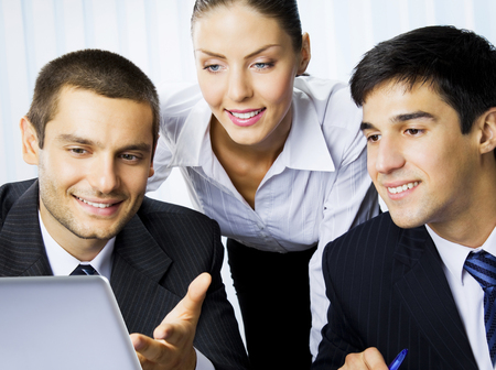 Three happy smiling successful businesspeople working with laptop at office. Success in business and teamwork concept. photo