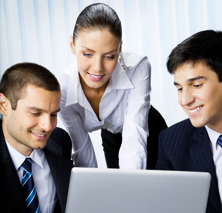 Three happy smiling successful business people working with laptop at office. Success in business and teamwork concept. photo