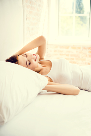 Portrait of beautiful young happy smiling woman waking up at bedroom Stock Photo