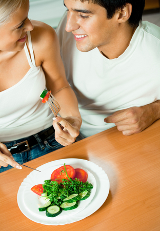 Young happy couple eating salad at home together Stock Photo