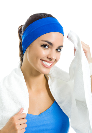 Portrait of happy smiling young woman in fitness wear with towel, isolated over white background. Workout, fit and sport training concept.