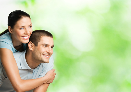 Portrait of young happy smiling attractive couple outdoors, with copyspace. Love, dating and relationships concept. photo