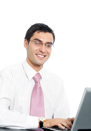 Portrait of young happy smiling businessman in glasses working with laptop, isolated over white background. Success in business concept studio shot. photo
