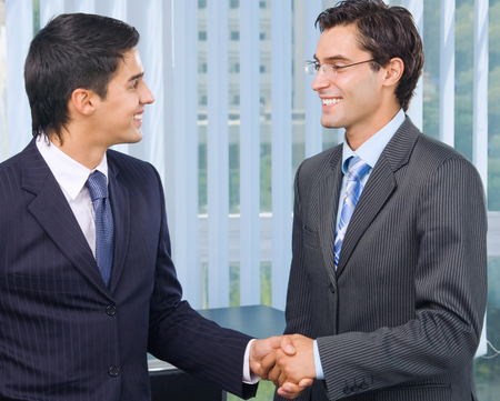 two hands: Two happy smiling businesspeople, or businessman and client, handshaking at office. Success in business and teamwork concept. Stock Photo