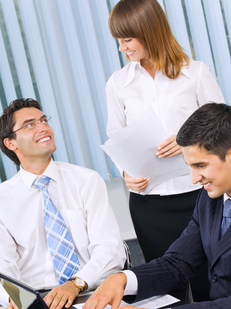 Three happy smiling businesspeople working with document at office. Success in business and teamwork concept. photo