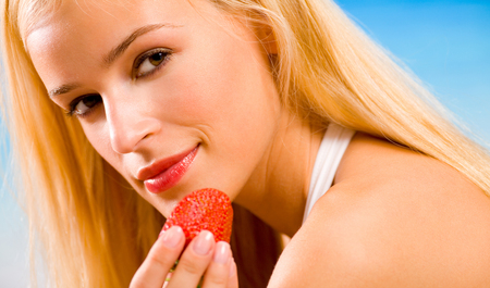 heathy diet: Young beautiful woman with strawberry on beach
