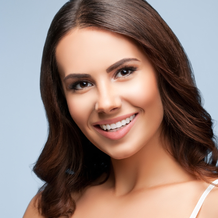 Portrait of beautiful cheerful smiling young woman, on grey background