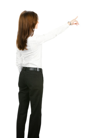 Full body of young businesswoman pointing at something in her back, isolated on white background. Success in business concept studio shoot. photo