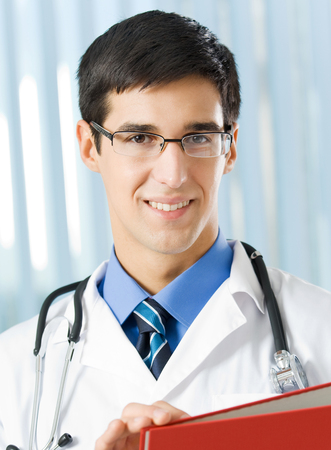 healthcare portrait: Portrait of happy smiling young doctor with red folder, at office. Medicine, lab and healthcare concept. Stock Photo