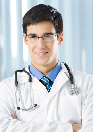 healthcare portrait: Portrait of happy smiling young doctor at office. Medicine, lab and healthcare concept. Stock Photo
