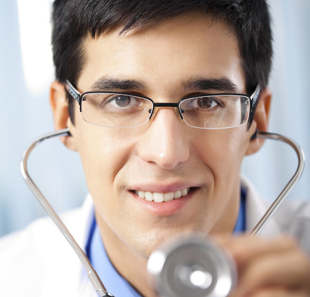 Happy smiling young doctor with stethoscope, at office. Medicine, lab and healthcare concept.