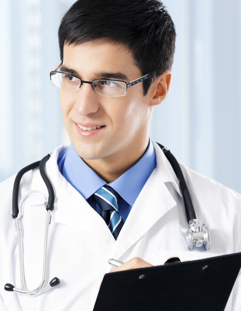 healthcare portrait: Portrait of happy smiling young doctor with clipboard at office. Medicine, lab and healthcare concept. Stock Photo