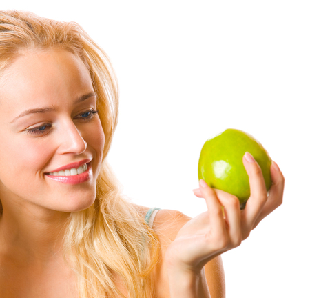 Portrait of young attractive happy smiling woman looking at apple, isolated over white background. Healthy eating concept studio shoot. photo