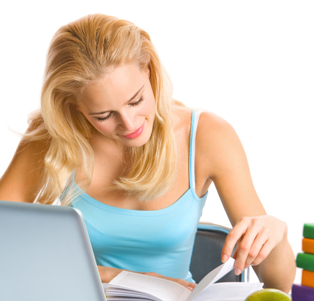 Young woman learning with textbooks and laptop, isolated over white background. Education concept studio shoot. photo